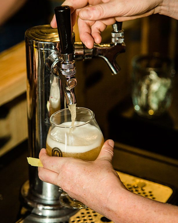 Closeup of hands pouring draft beer into a goblet-style glass