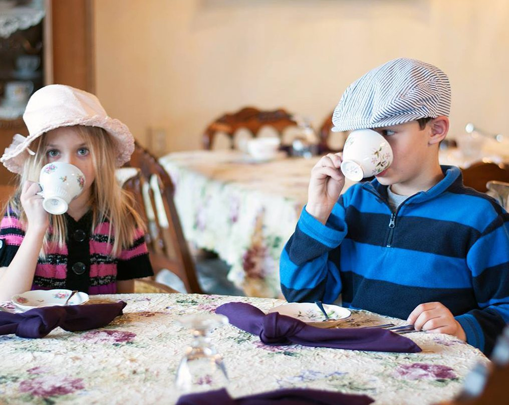 Two children in hats sit around a beautiful table sipping from fancy teacups