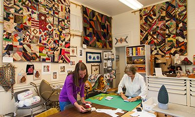 Two women cut and measure fabric with quilts mounted on the walls around them