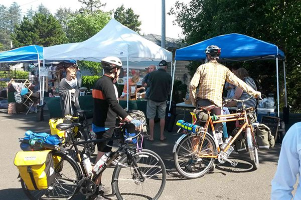 Two people walk their bikes through farmers market tents