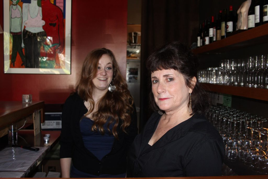 Two women stand behind the bar with wall of wine glasses behind them