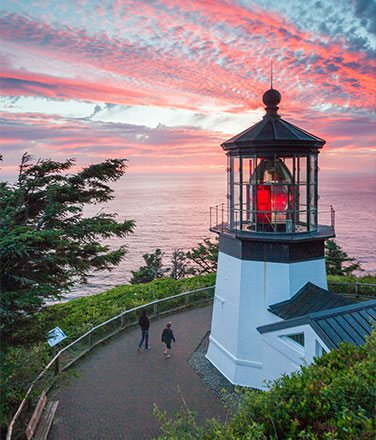 Aerial view of Cape Meares Lighthouse at sunset with pink clouds in the sky