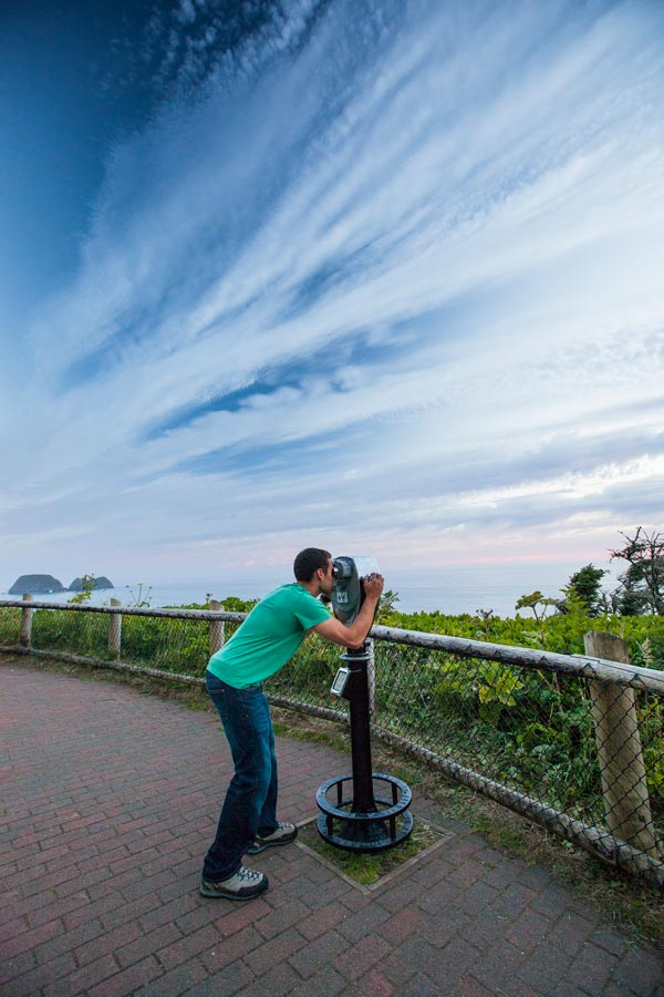 Man looks through coin-operated binoculars outside Cape Meares Lighthouse