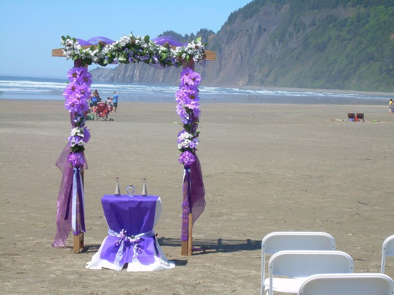 Wedding arch decorated with purple fabric and flowers on the beach