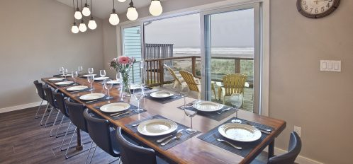 Long dining table, fully set, in front of a window